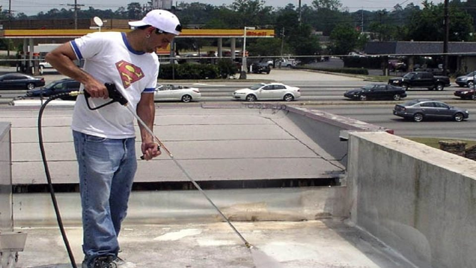 A person using the concrete cleaner in a pressure washer to clean concrete roof