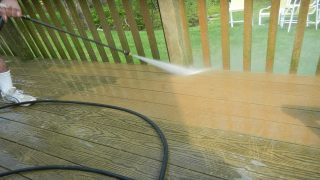 A person cleaning a wooden deck with a pressure washer