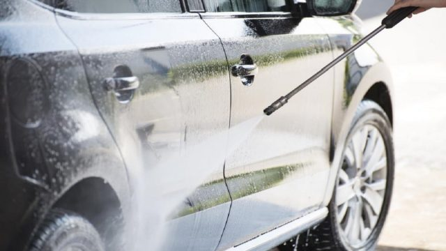 A car being cleaned with a pressure washer