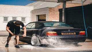 A man washing a car with a pressure washer